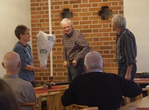 Tomas räcker över en blomma till föreläsarna. Jan Johansson och Marie Friberg.